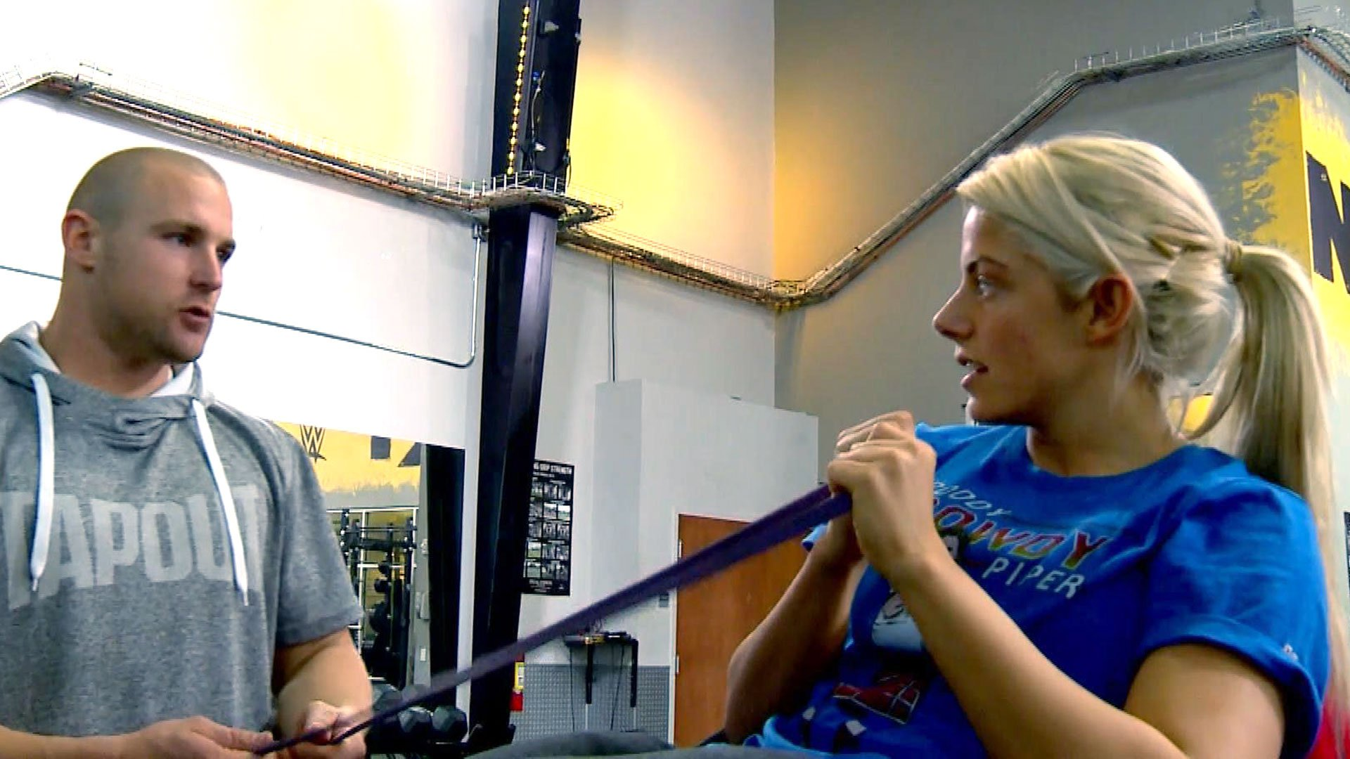 Sean Hayes coaches Alexa Bliss through a set of Russian twists