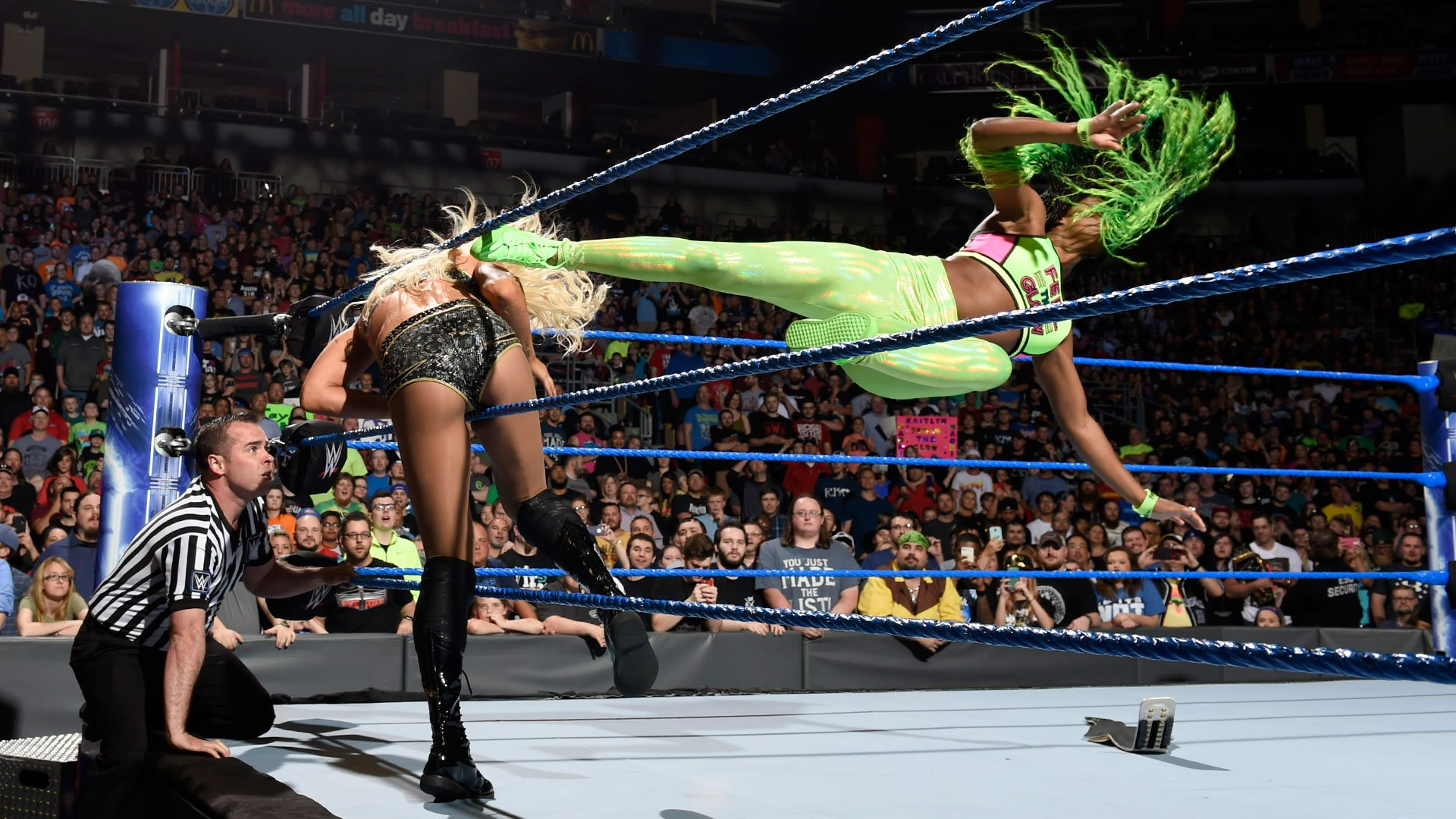 Naomi dropkicks Charlotte out of the ring.