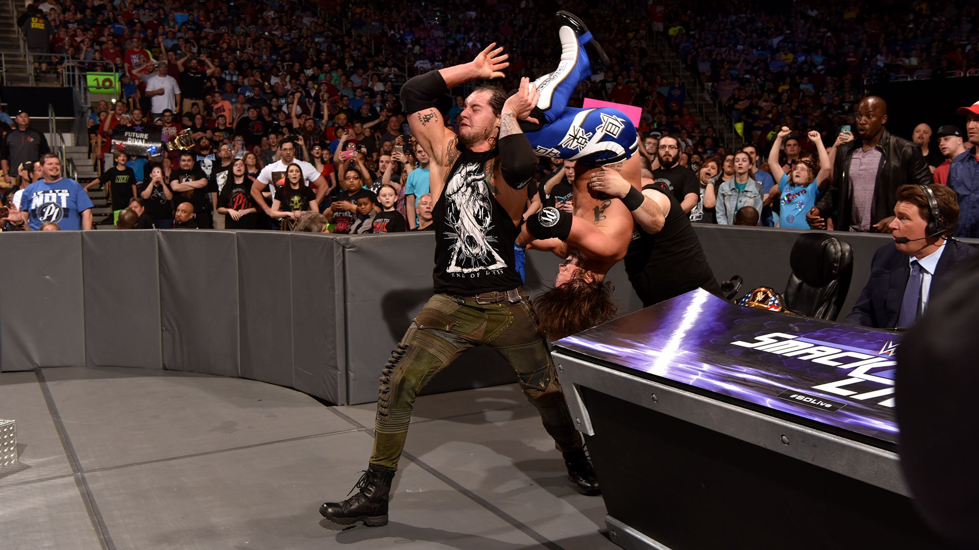 Corbin flips The Phenomenal One onto The Prizefighter.