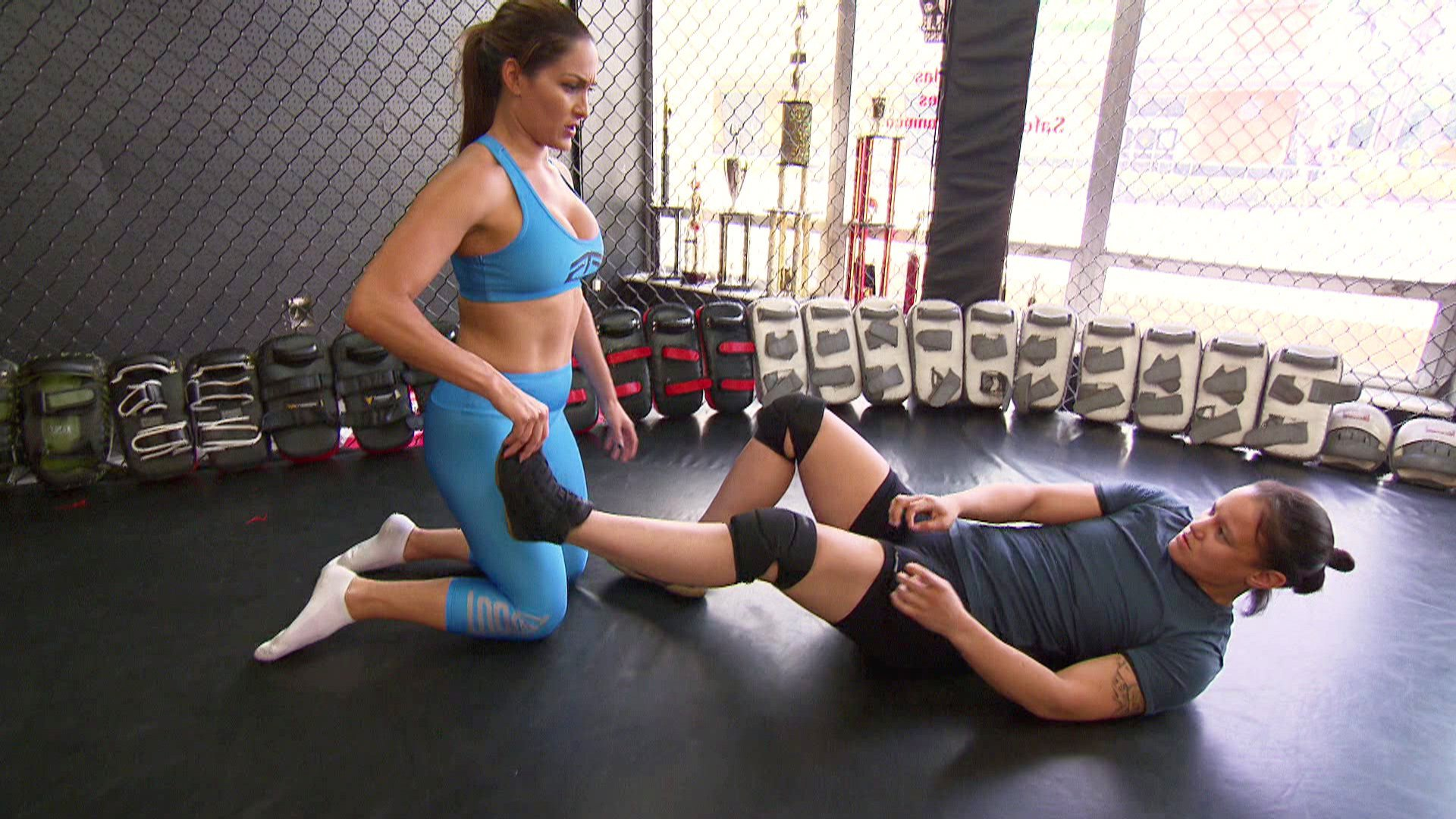 Nikki, Nattie and MMA fighter Shayna Baszler attempt to work out a new submission hold. for Nikki.