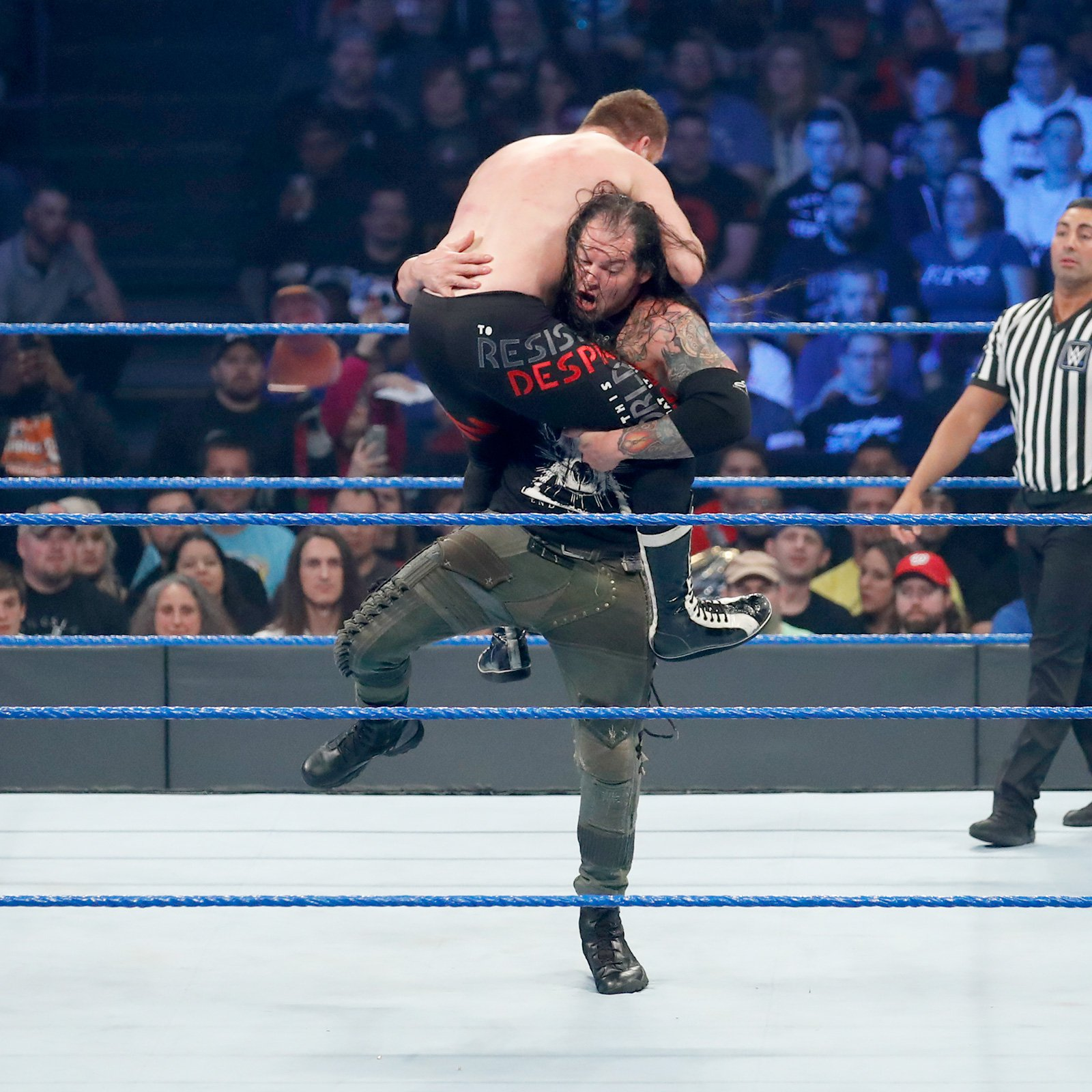 Corbin takes down Zayn with a powerful slam.