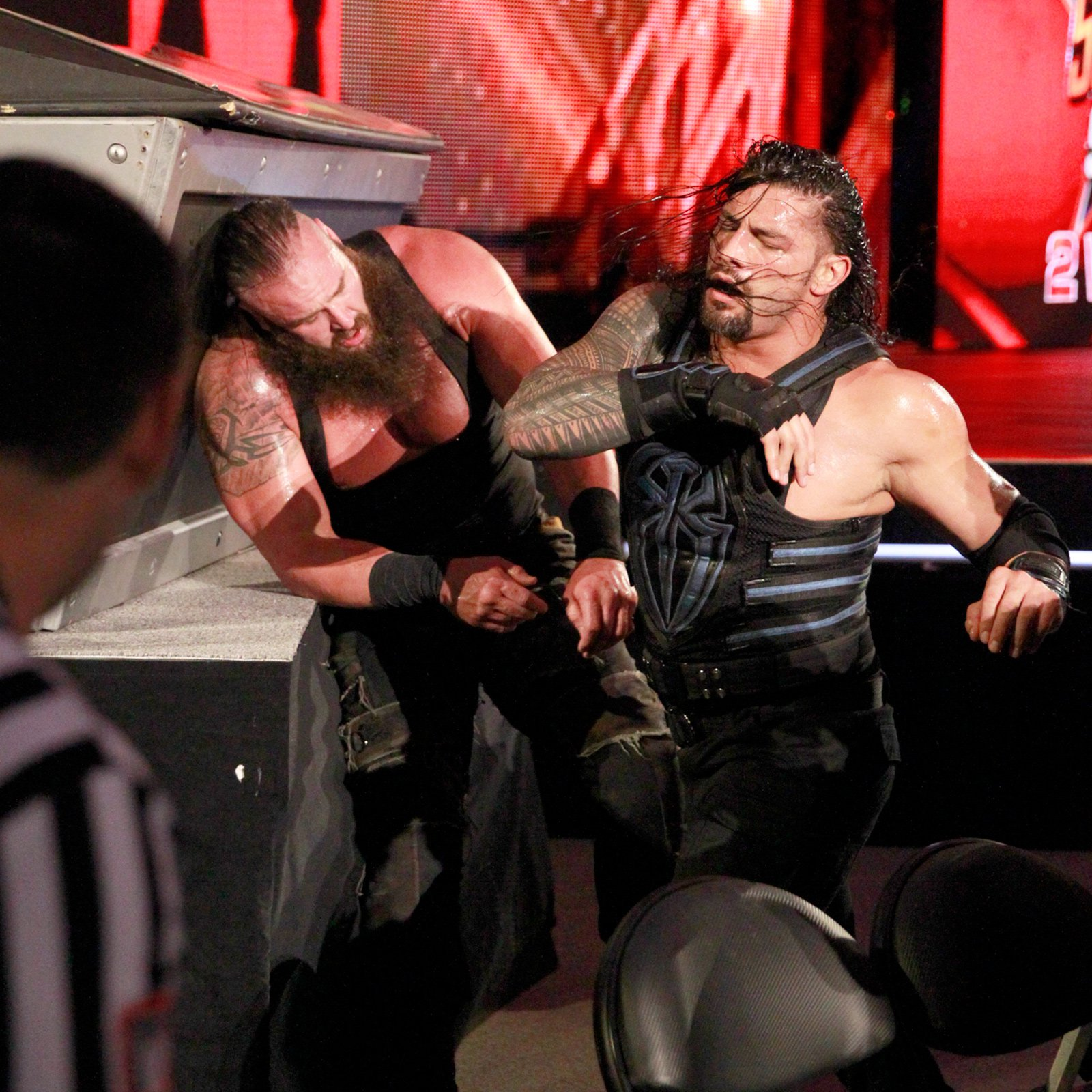 Reigns and Strowman continue to trade blows near the announce table.
