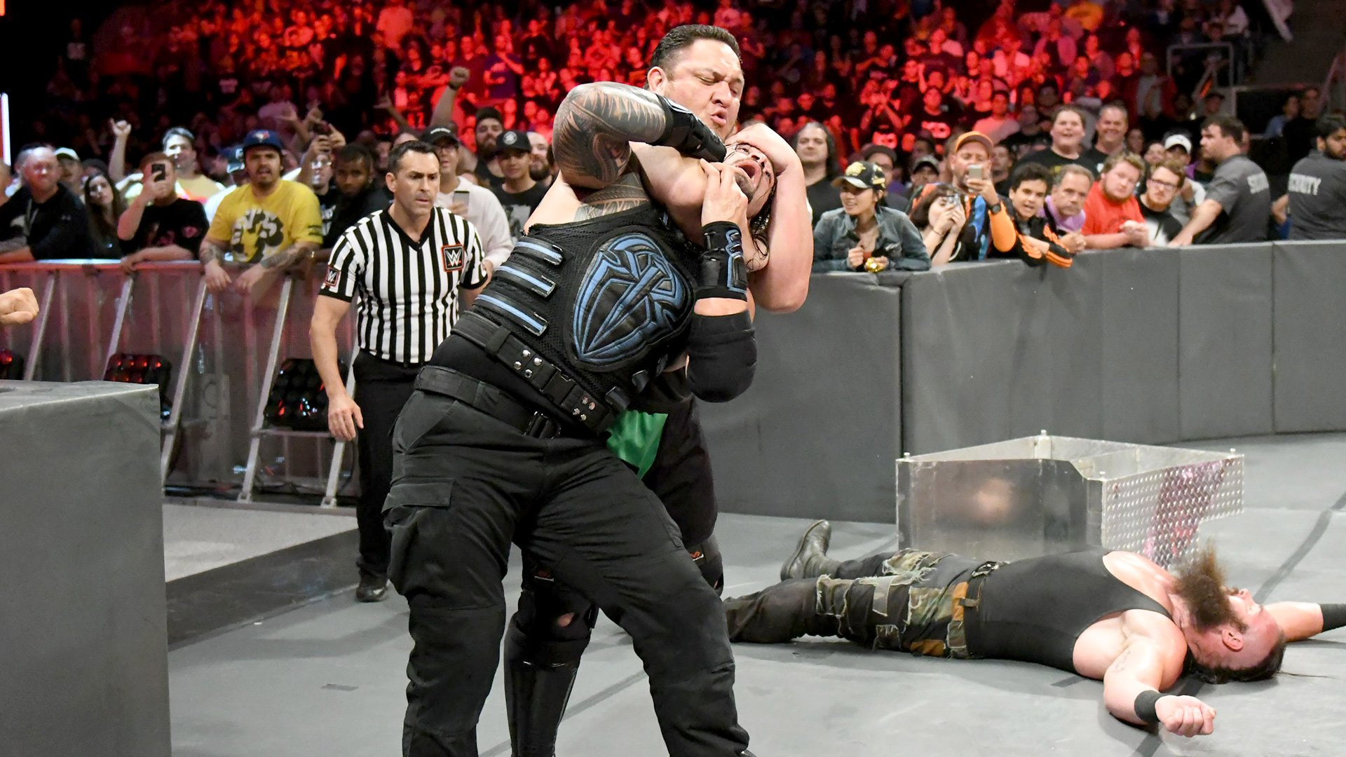 Suddenly, Samoa Joe emerges from the crowd and locks Roman Reigns in the Coquina Clutch!