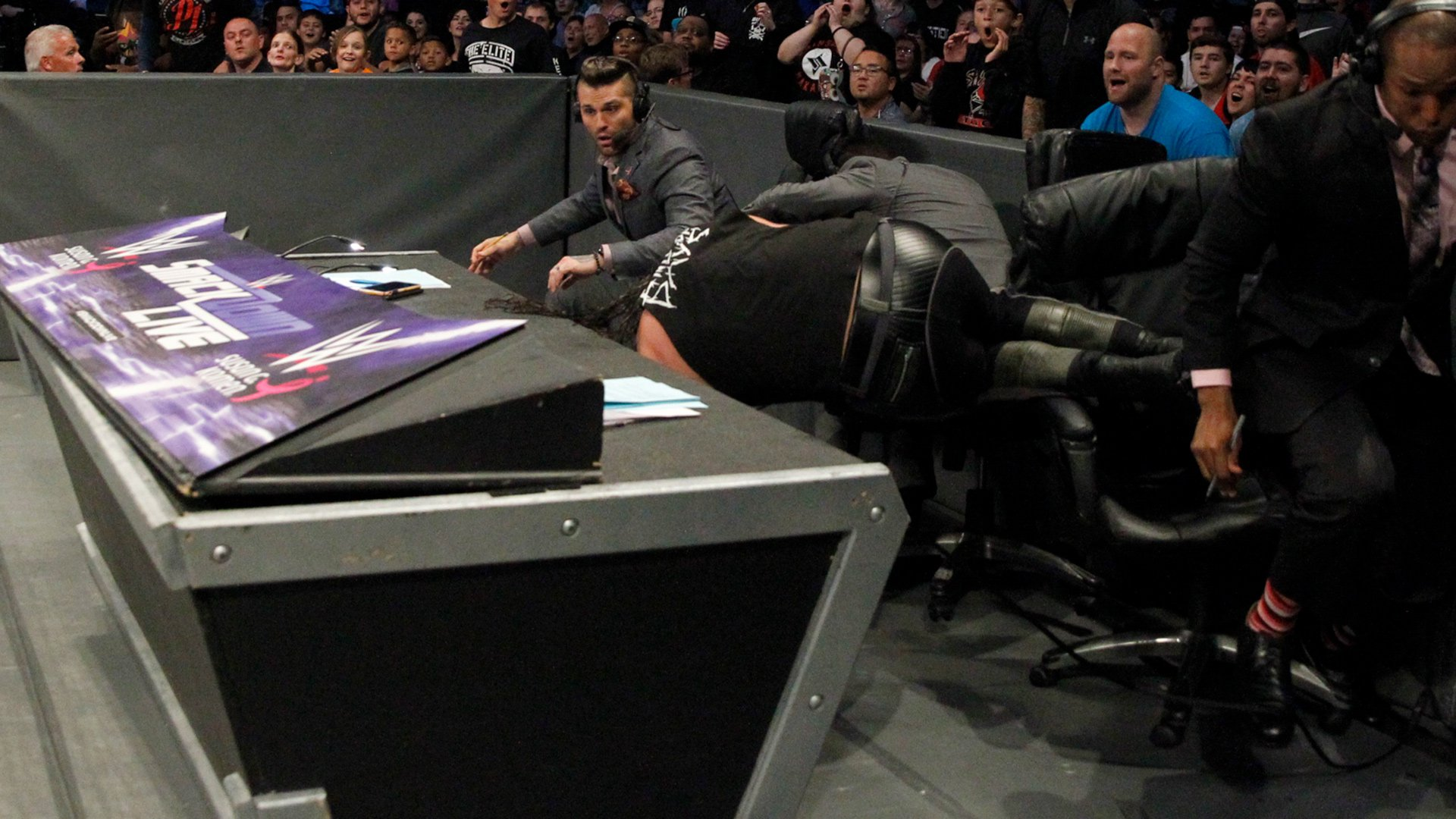 Styles lands a dropkick to send Corbin plummeting over the announce table!