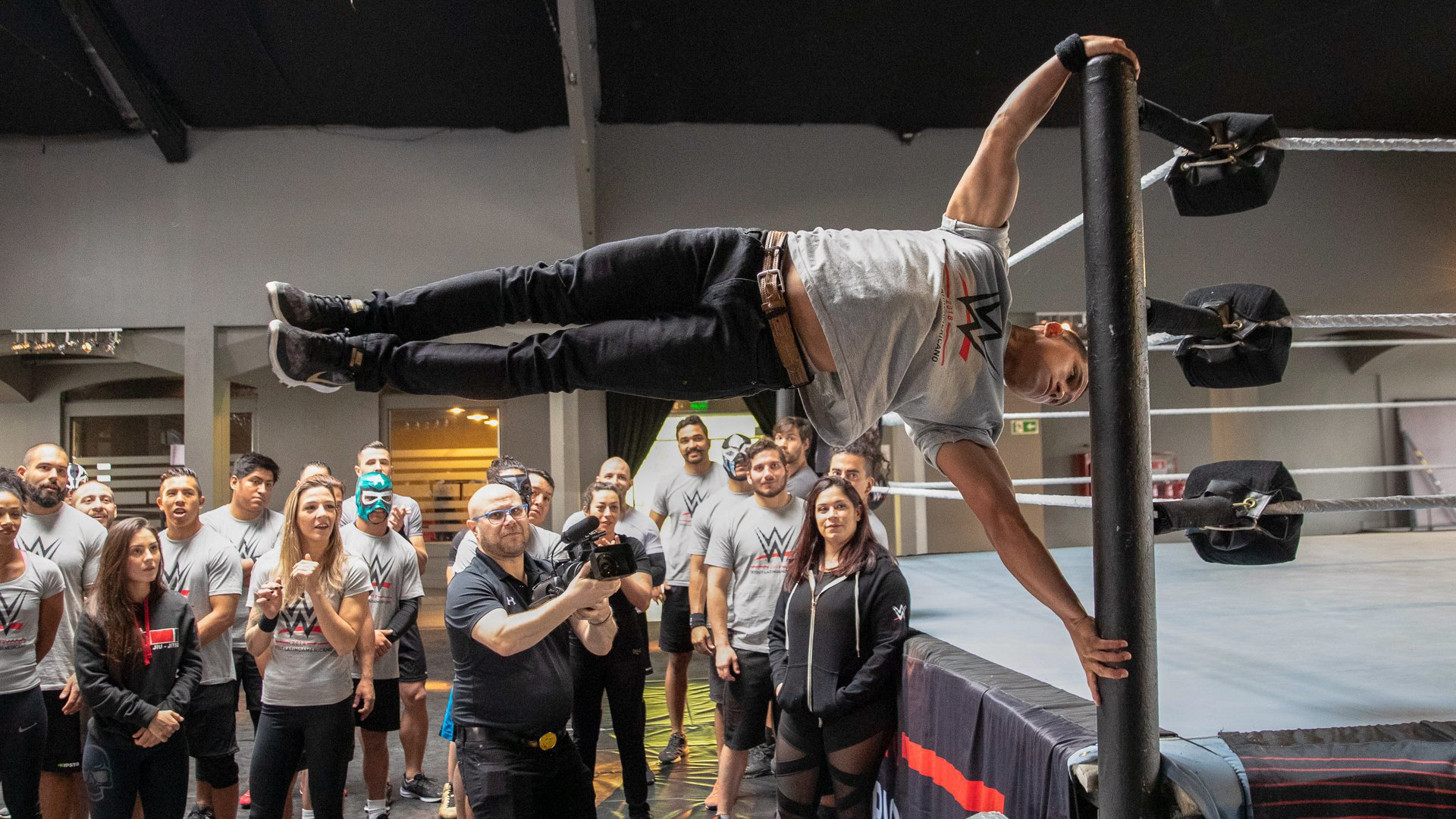 Chilean street-workout athlete Pedro Sanchez impresses the other prospects as he performs the human flag on the ring post.