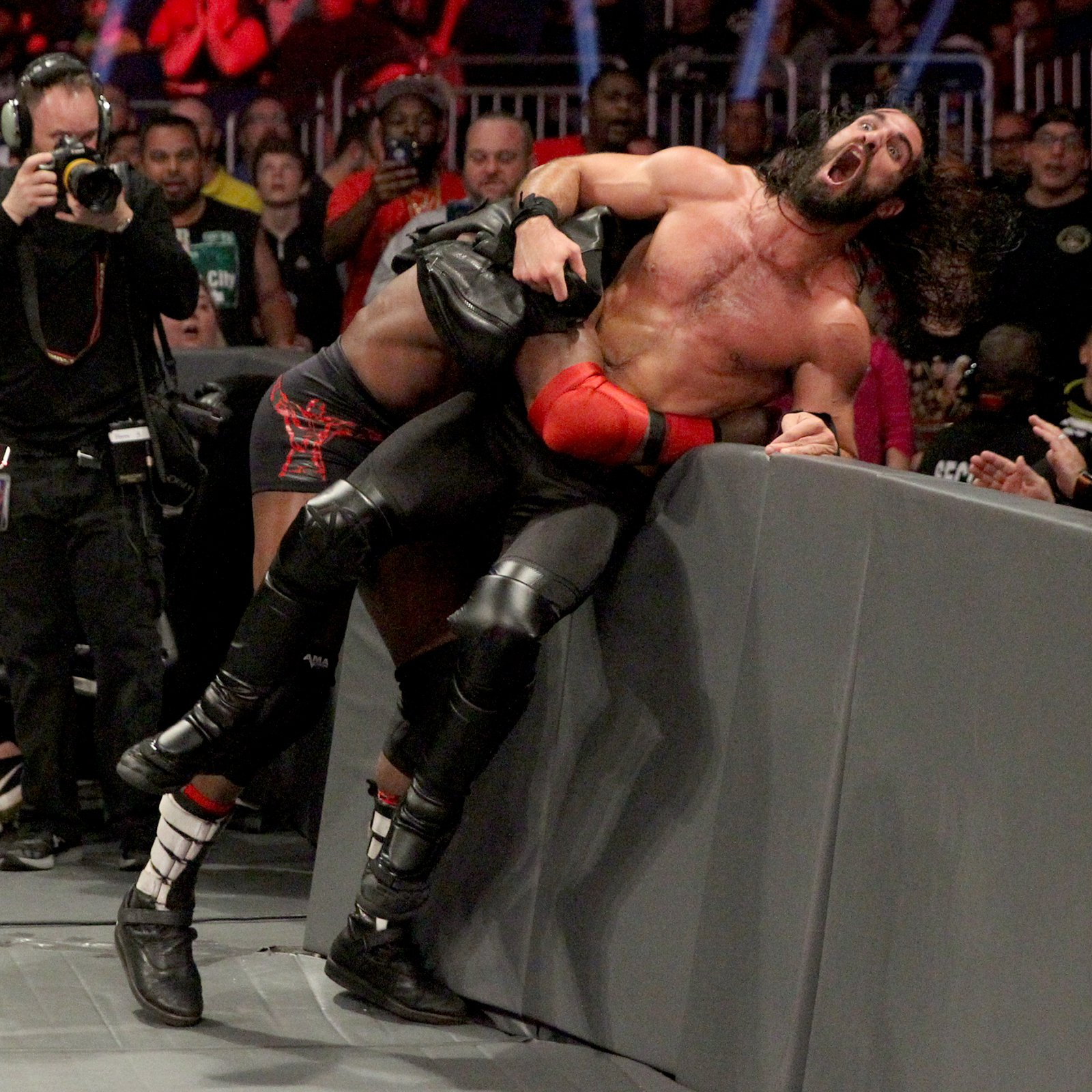 Lashley drives Rollins into the barricade...