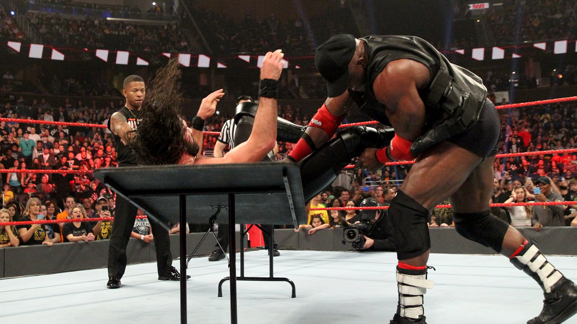 Lashley drives Rollins through the table...