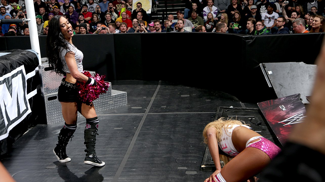 AJ mocks Cameron with her pom pons at ringside.