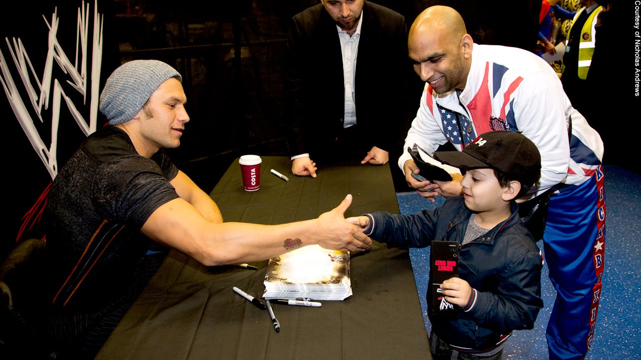 Fandango greets a young member of the WWE Universe as he signs autographs and poses for pictures.