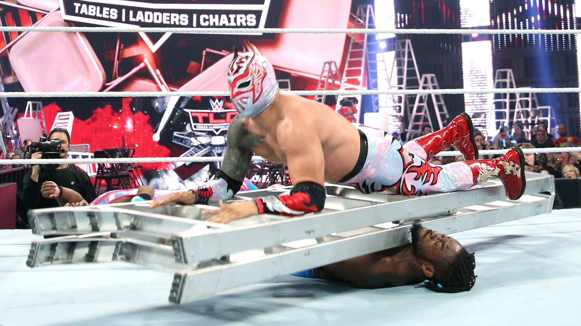 Sin Cara squashes Kofi Kingston with a wince-inducing ladder collision.