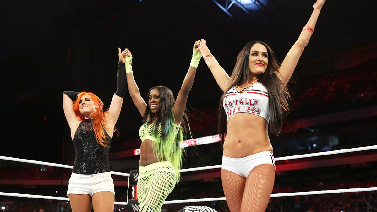 Naomi celebrates pinning the SmackDown Women's Champion with her tag team partners.