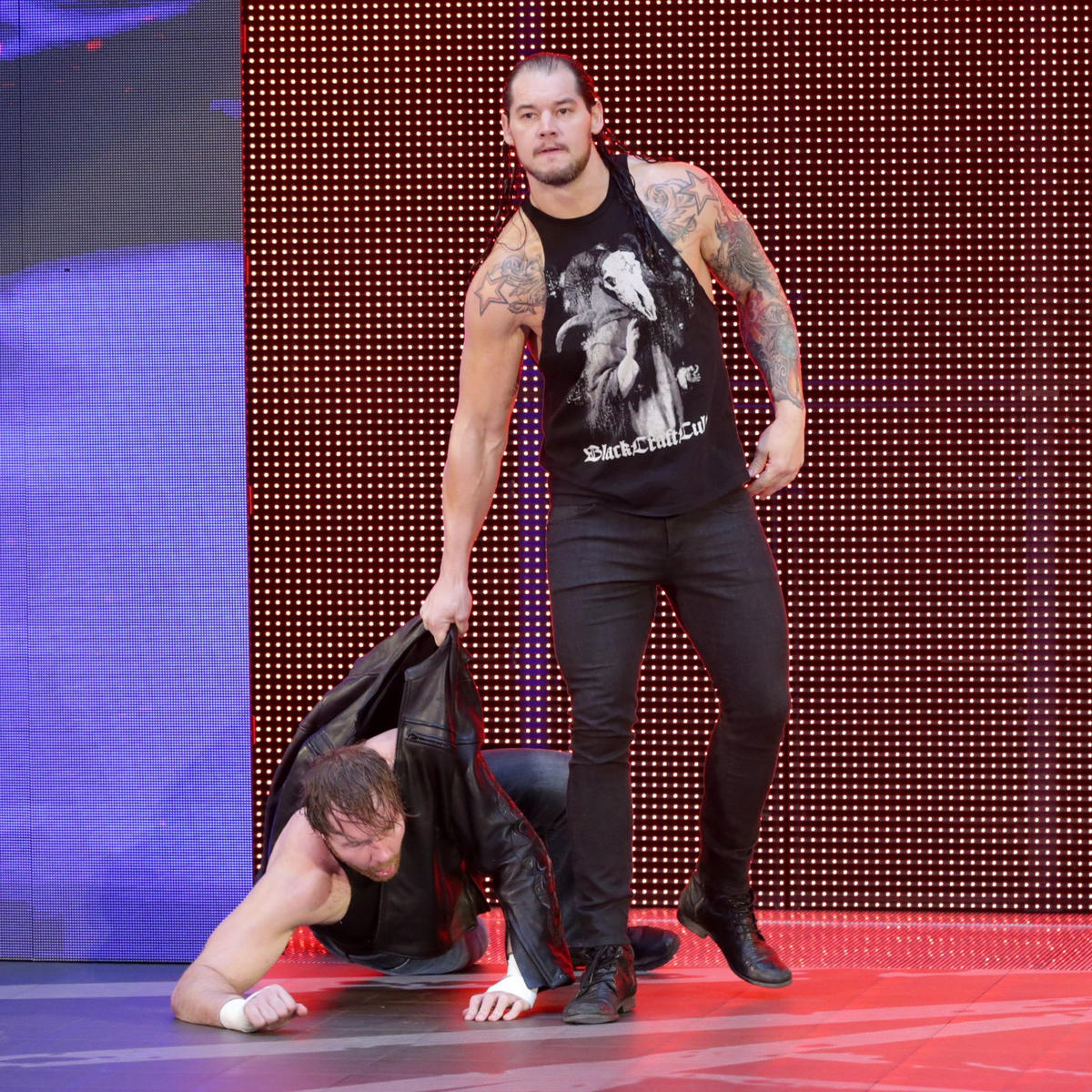 Baron Corbin drags Ambrose out onto the stage.