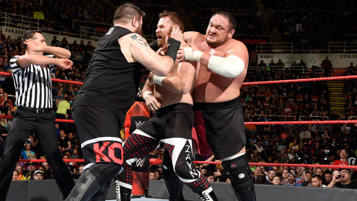 Joe holds Zayn's arms while Owens hammers away.