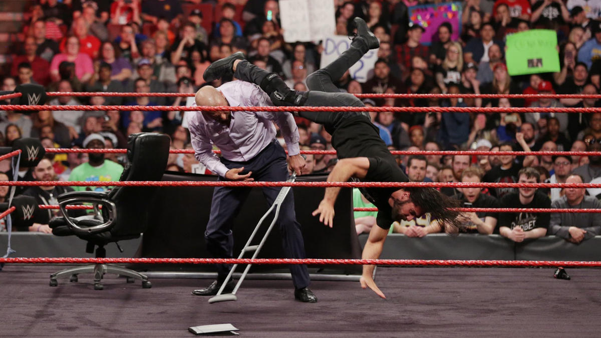 Rollins fights back by kicking Triple H in the head.