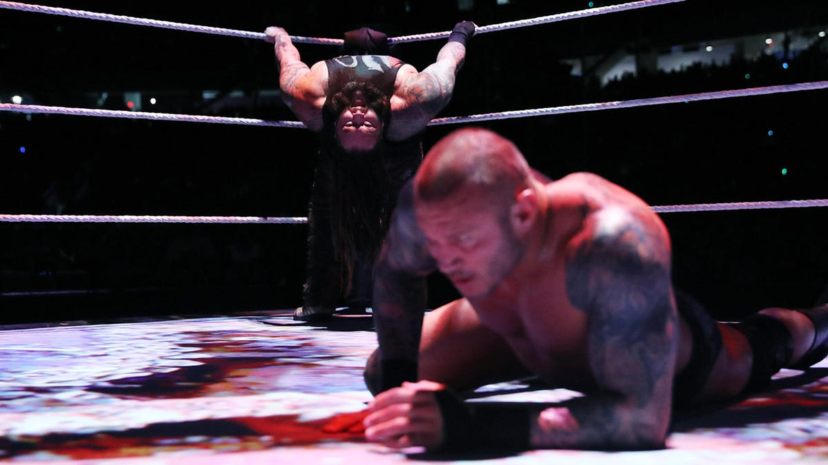 Wyatt distracts Orton with disturbing images on the ring canvas.