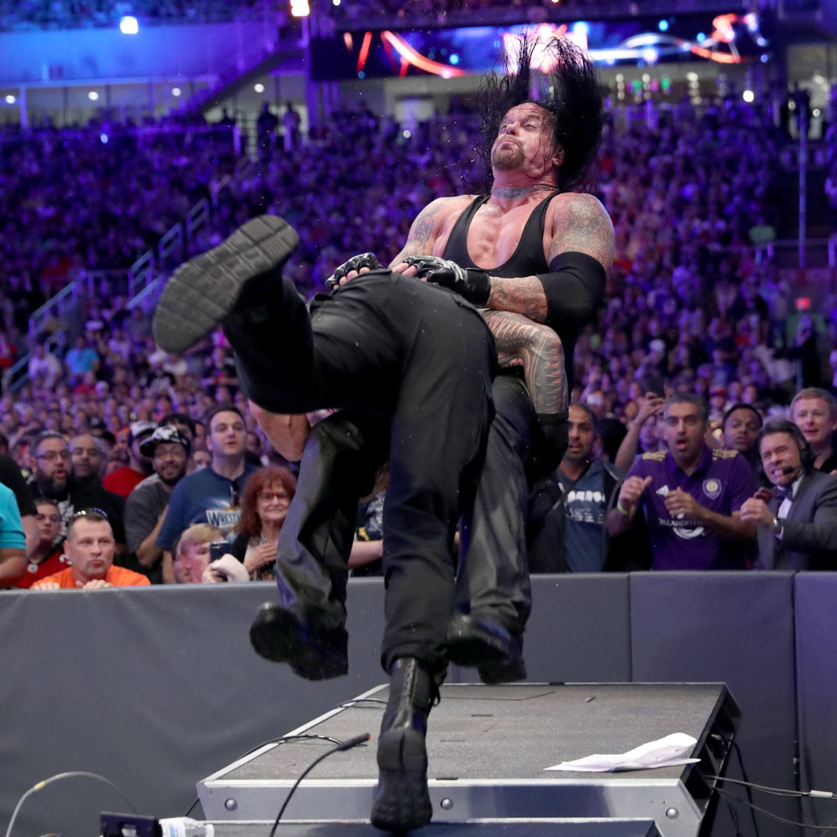 Undertaker menerima rempuhan bahu daripada Roman Reigns