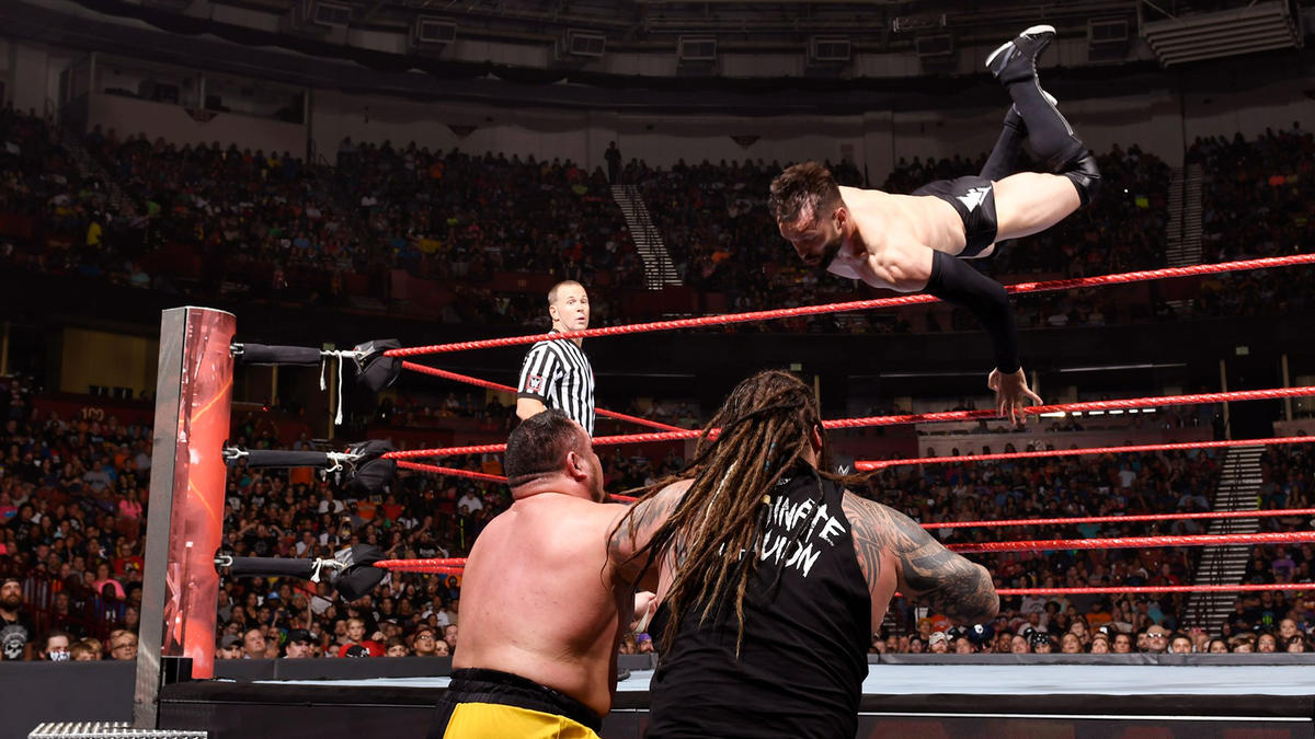 Bálor launches himself over the top rope and onto both of his adversaries.