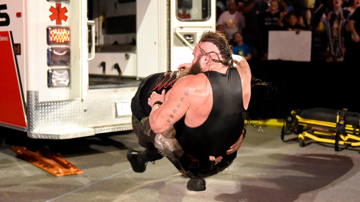 But Reigns reemerges from the ambulance and takes down Strowman with a Spear!