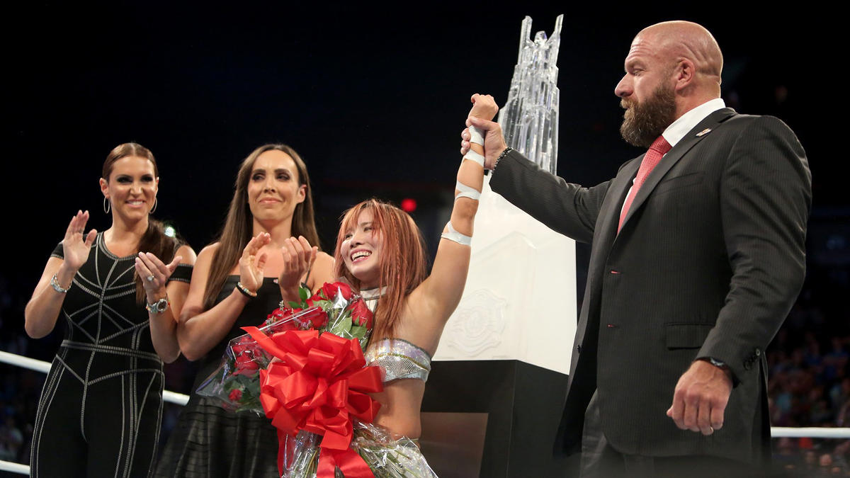 Chief Brand Officer Stephanie McMahon, NXT Assistant Head Coach Sara Amato, and Chief Operating Officer Triple H present Sane with the trophy.