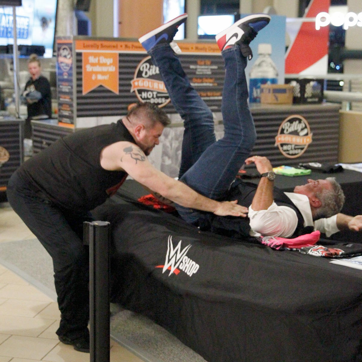Owens savagely powerbombs Shane through the merchandise table!