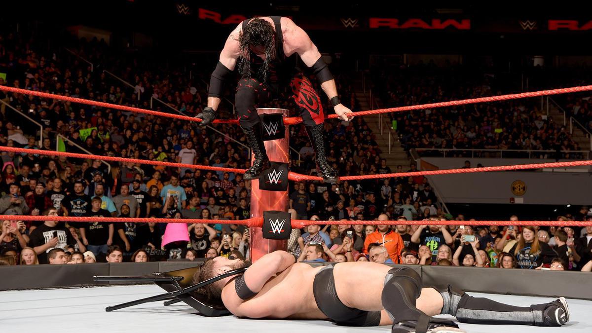 Kane wraps a chair around Balor's throat...