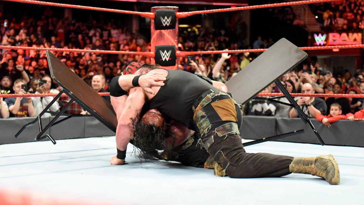 ... and drives Kane through the table with a Running Powerslam!