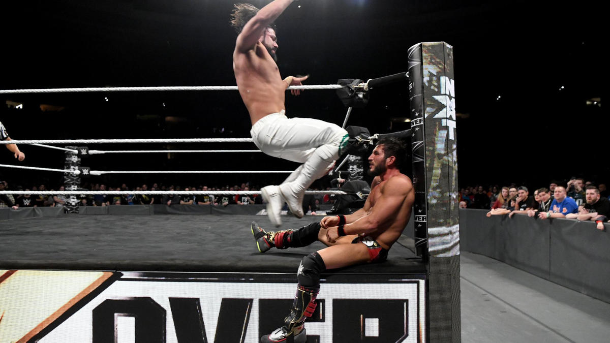 Almas hits his opponent with a double knee strike against the ring post.
