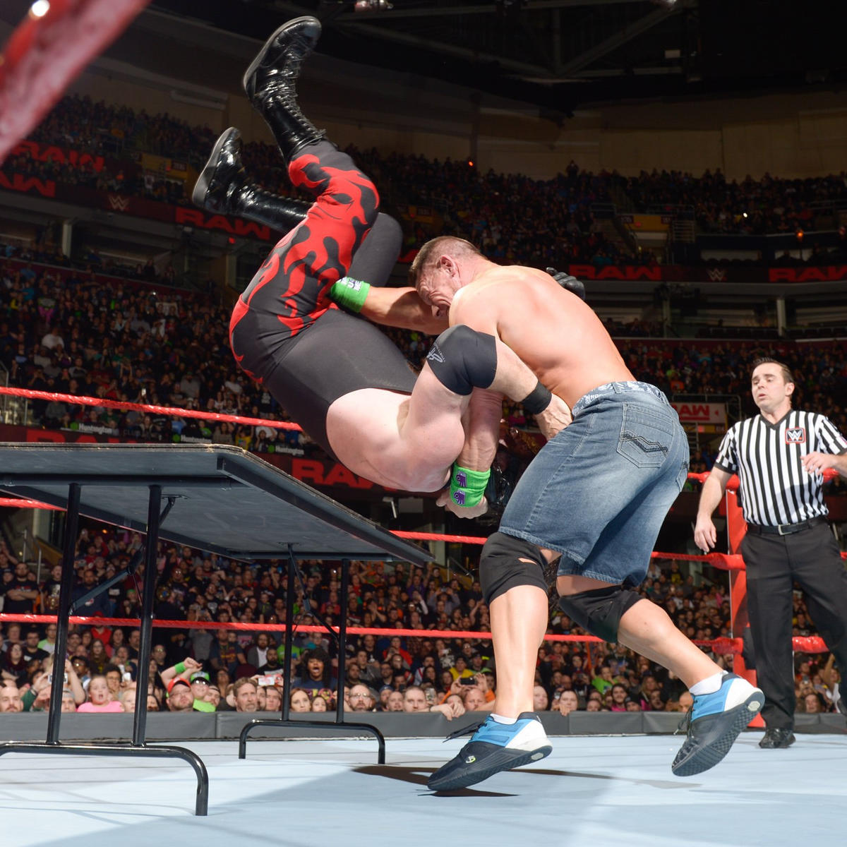 Cena drops Kane with a thunderous Attitude Adjustment through a table and gets the 1-2-3!