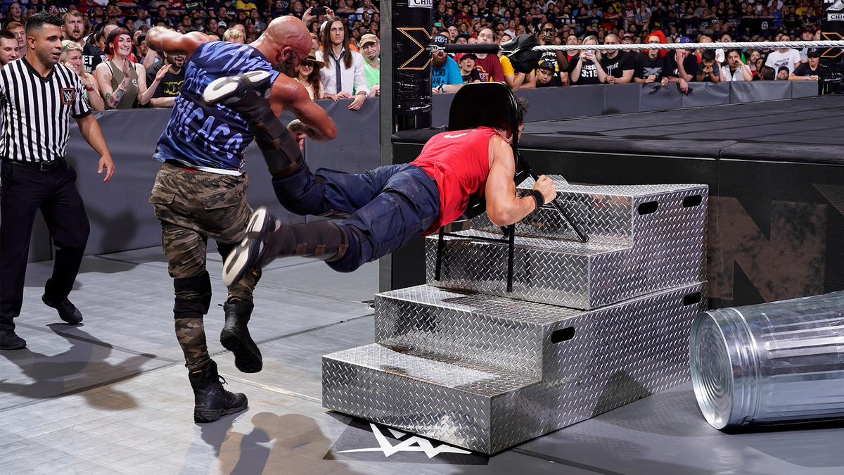 ... then wraps Johnny's neck in a chair and hurls him into the steel steps!