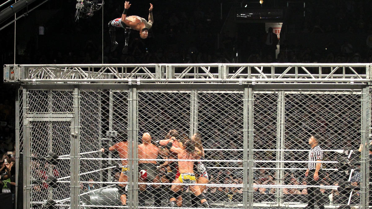 Ricochet hits a double rotation moonsault from the top of the cage!