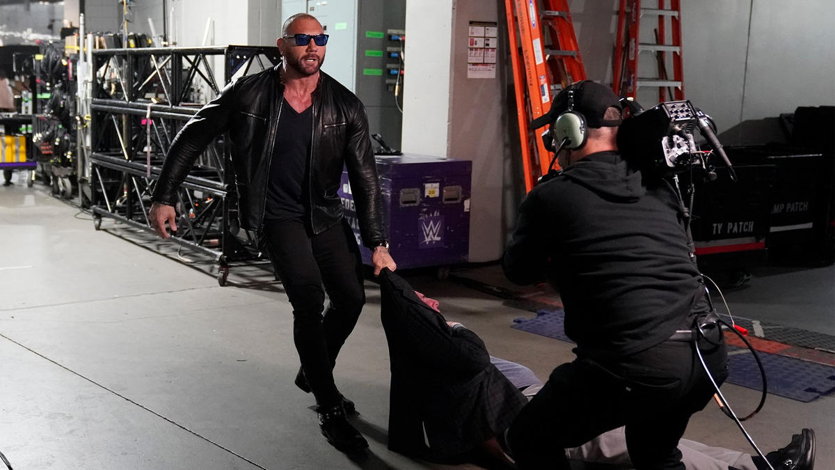 "After disappearing into Flair's locker room, The Animal soon returns to the hallway, dragging ""The Nature Boy"" with him."