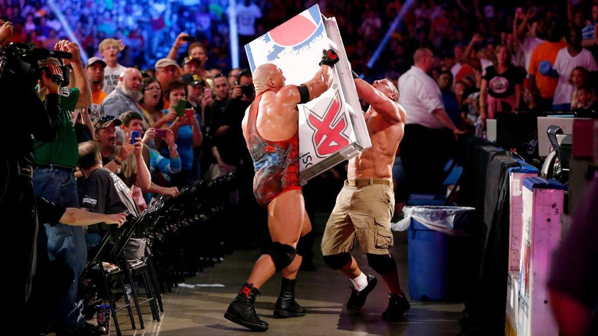 The No. 1 contender slams Cena with a board.