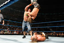 John Cena dumps Shawn Michaels onto Triple H at Survivor Series 2009.