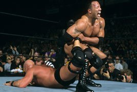 The Rock puts Steve Austin in the Sharpshooter.