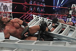 Triple H puts Kevin Nash in a figure four around the ladder