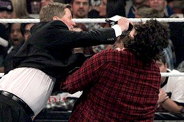 John Laurinaitis hits Mick Foley with a microphone